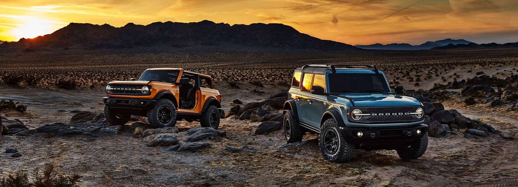 Two 2021 Ford Broncos in the desert at sunset