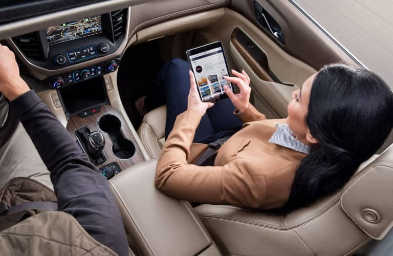 woman_sitting_in_passenger_seat_of_car_enrolling_in_My_GMC_Rewards_on_tablet_o
