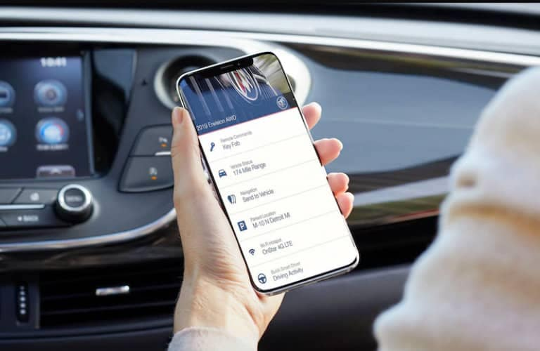 person_holding_phone_with_Buick_Connected_Services_app_in_car_o