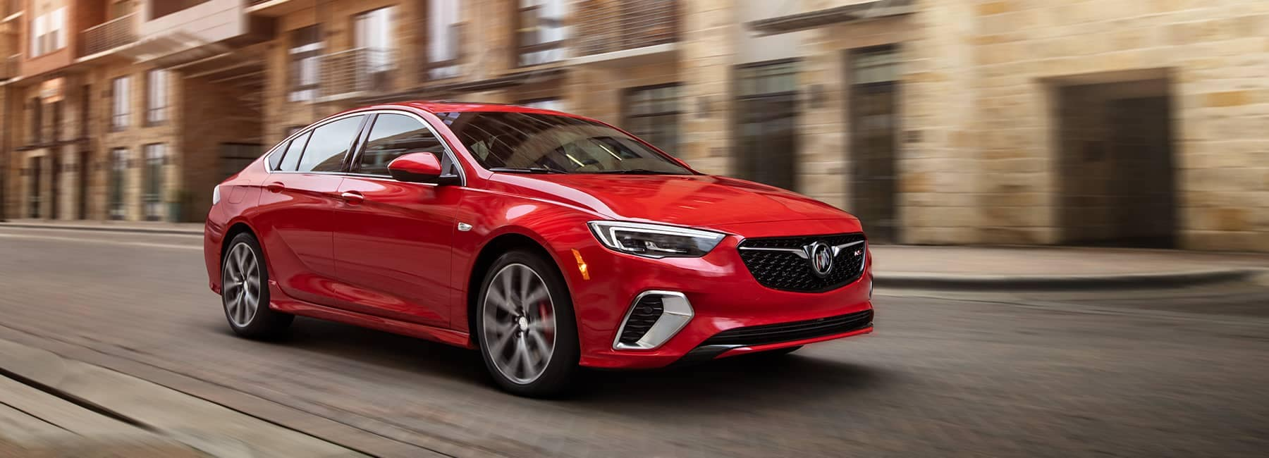 Red 2020 Buick Regal Sportback cruising down the street