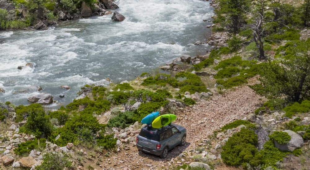 A blue 2021 Ford Bronco Sport is shown from a high angle driving next to a river on a rocky path.