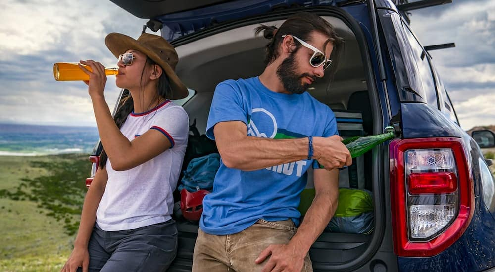 Two people are shown leaning against the rear of a 2021 Ford Bronco Sport while drinking beverages.