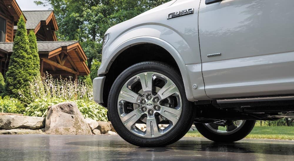 A close up shows the front wheel and tire on a 2016 Ford F-150 Limited.