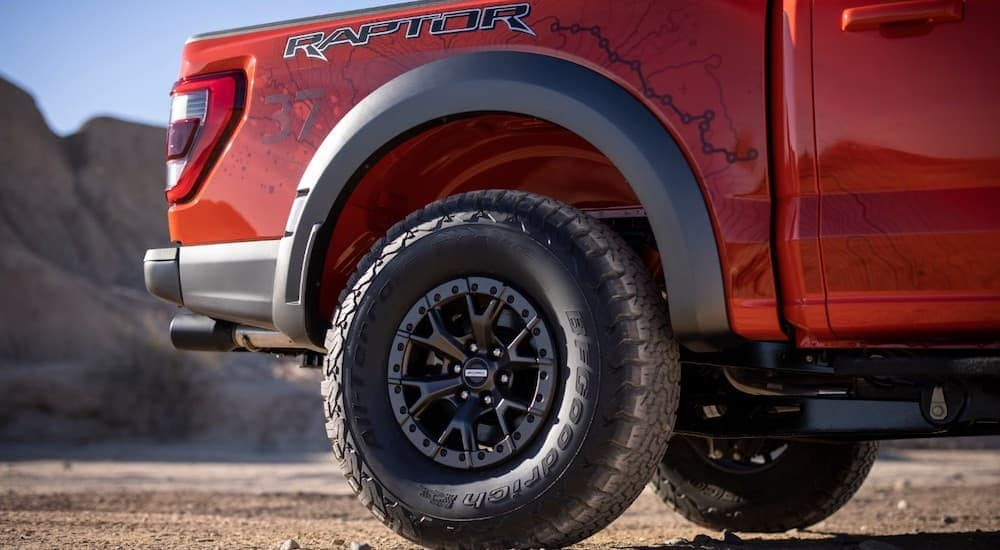 A close up shows the rear rim and tire on an orange 2021 Ford F-150 Raptor.