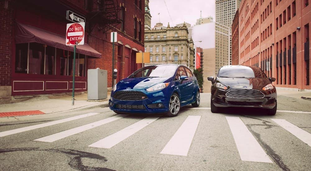 A blue 2015 Ford Fiesta ST and black fiesta are parked next to each other at a crosswalk.