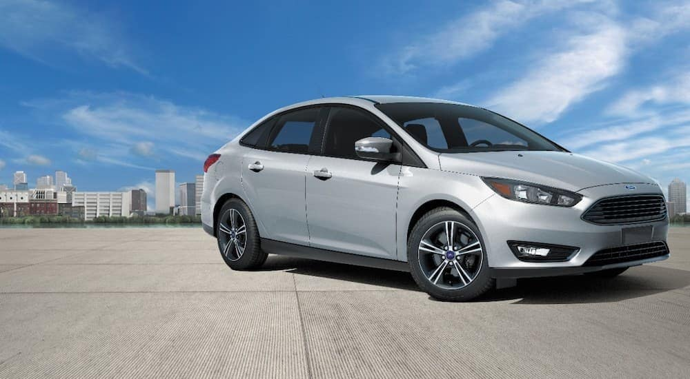 A silver 2017 Ford Focus is shown from the side with a city in the background after leaving Bullitt County Ford dealer.