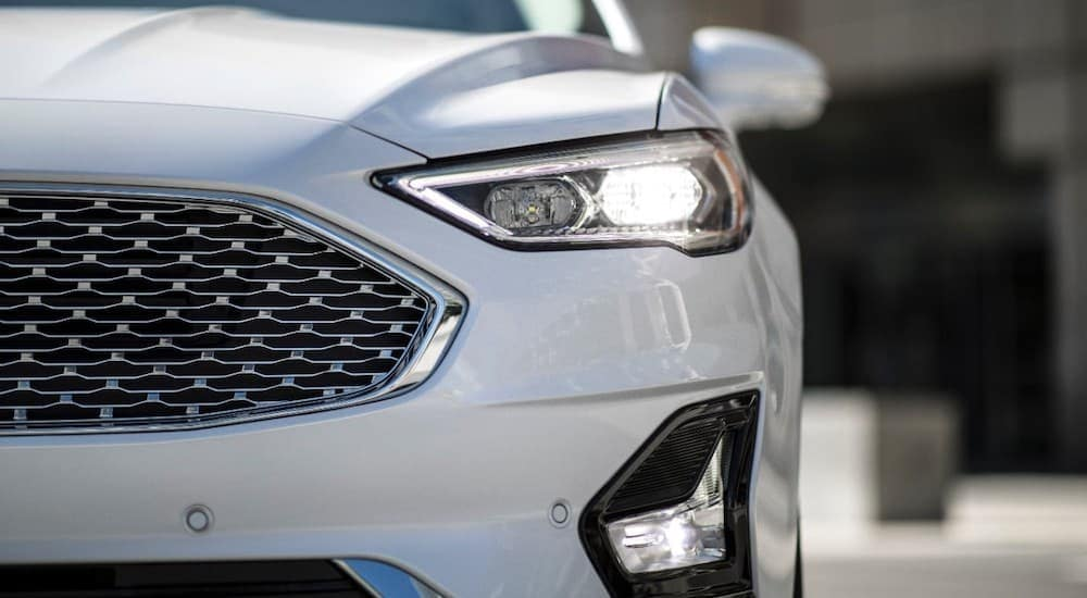 A close up shows the drivers headlight on a white 2020 Ford Fusion.