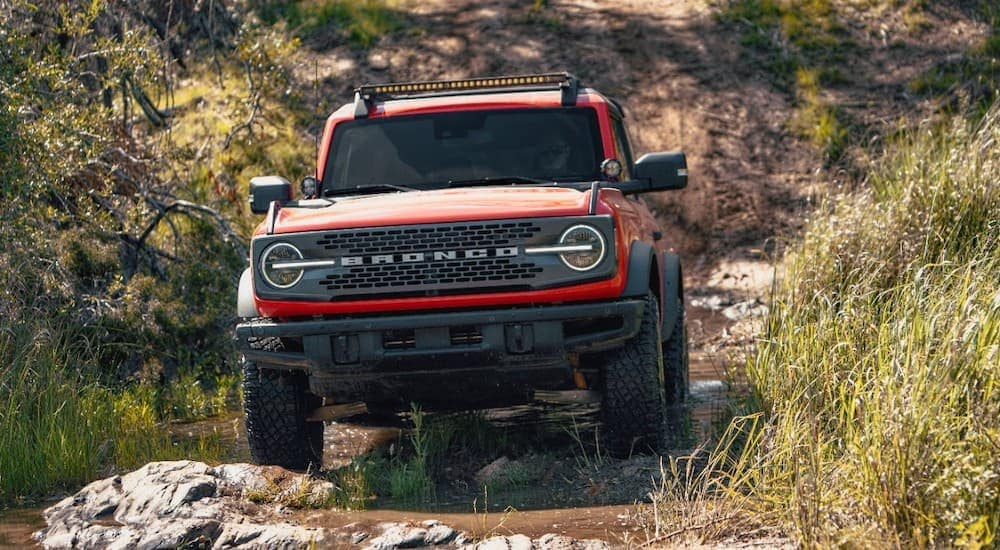 A red 2021 Ford Bronco Sport is shown off roading down a path after leaving a Mount Washington Ford dealership.