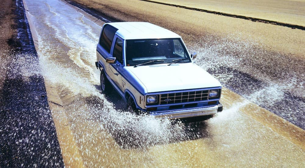 A white 1985 Ford Bronco II is shown driving down a wet road splashing through water.