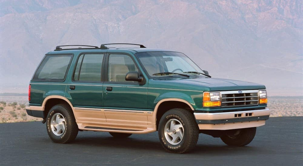 A green and tan 1993 Ford Explorer Eddie Bauer Edition is shown parked on tarmac.