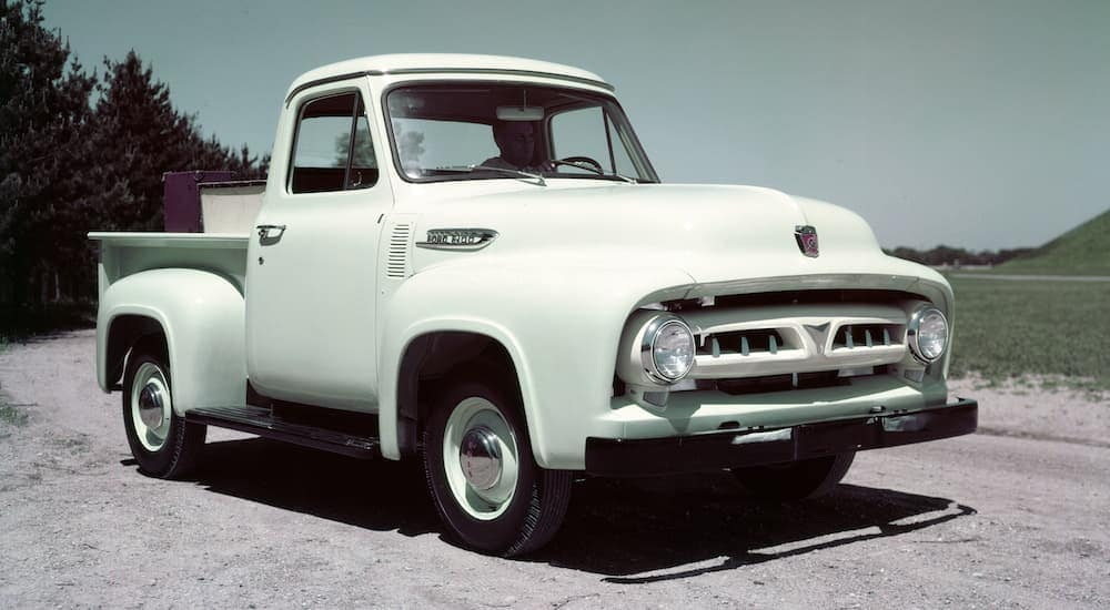 A pale blue 1953 Ford F-100 C460 is shown parked on a dirt path.