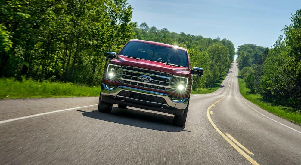 A red 2021 Ford F-150 is shown from the front driving down the highway after leaving a used Ford truck dealership.