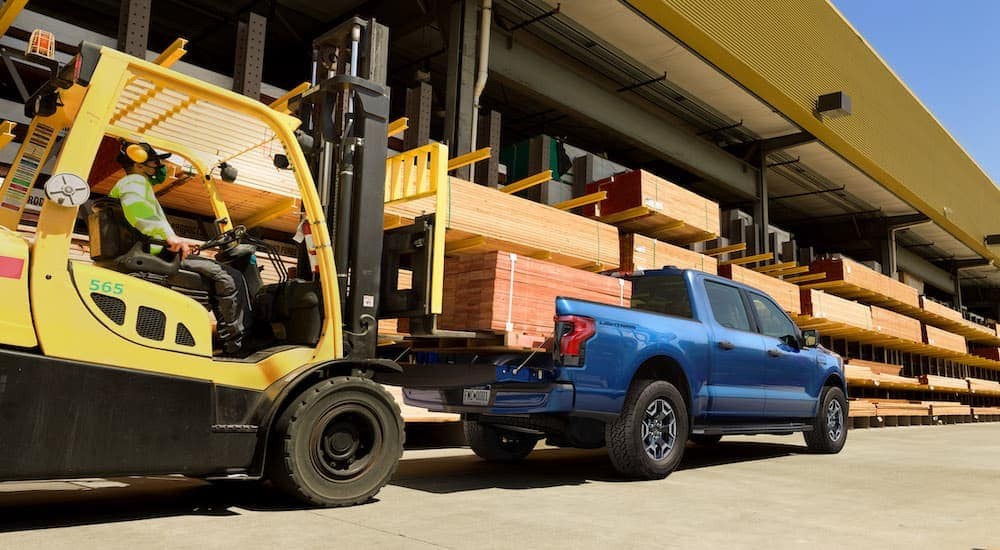 A blue 2022 Ford F-150 Lightning XLT is shown with wood being loaded in the bed by a yellow fork truck.