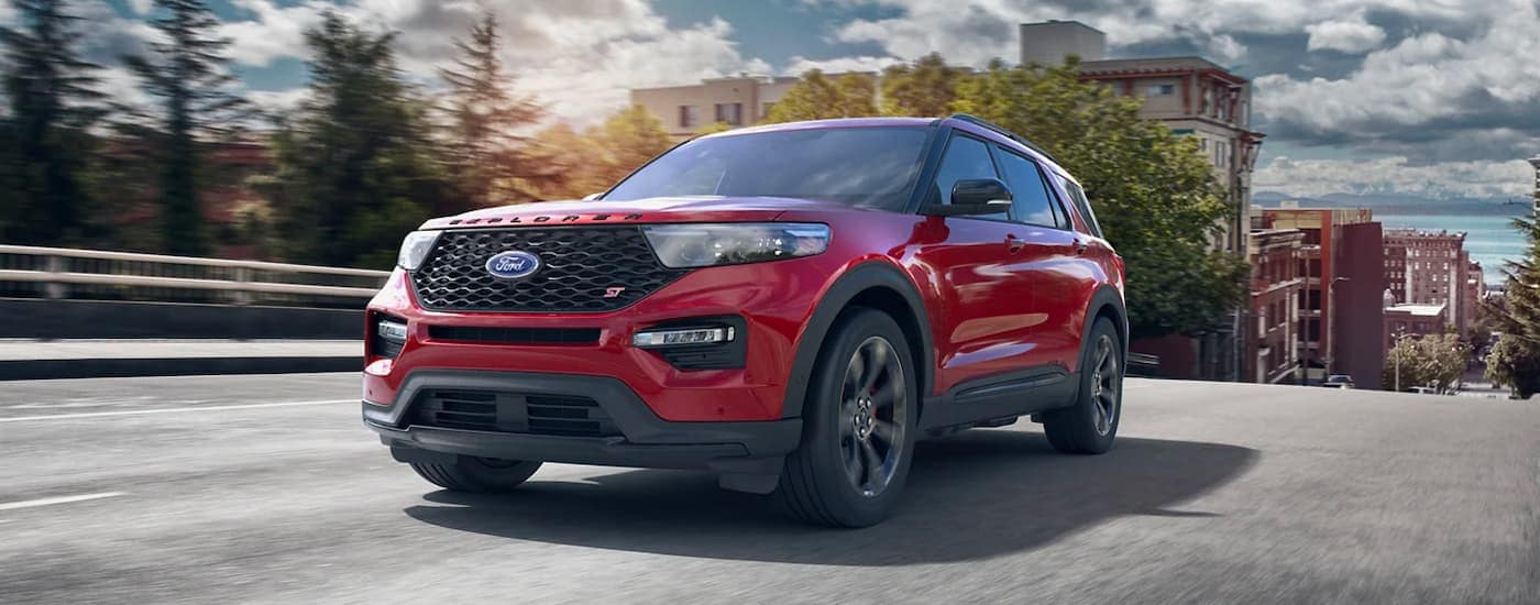 A red 2021 Ford Explorer ST is shown driving away from a city.