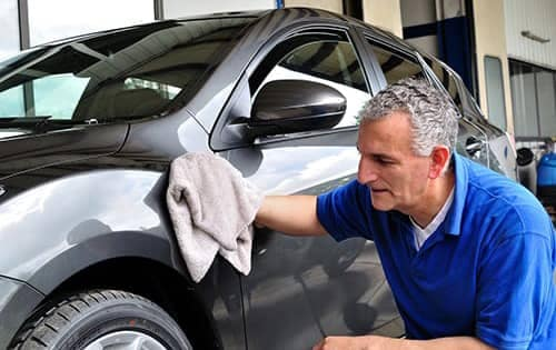 man is crouched down and wiping the fender of a car