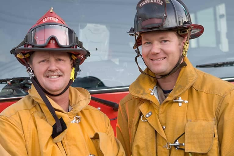 Two firefighters are standing in front of a fire engine