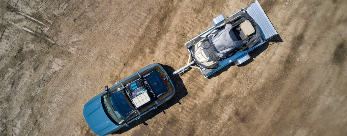 A blue 2021 Ford Bronco Sport Badlands 4-door is shown from a high angle towing a UTV after leaving a Ford Bronco Sport dealer.
