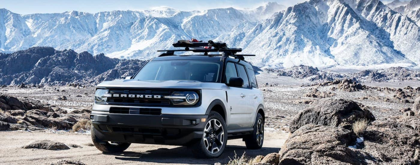 A silver 2021 Ford Bronco Sport 4-door is shown parked on a dirt path with snowy mountains in the background.