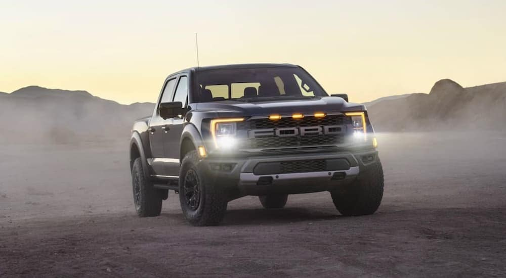 One of the most popular Ford performance vehicles, a black 2021 Ford Raptor, is shown parked on dirt with the headlights illuminated.