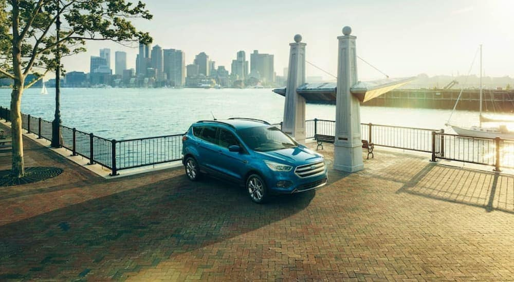 A blue 2017 Ford Escape Titanium is shown parked next to a bay overlooking a city.