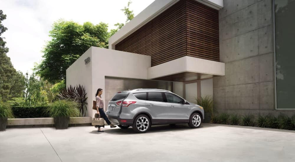 A silver 2013 Ford Escape is shown parked in a the driveway of a modern house.