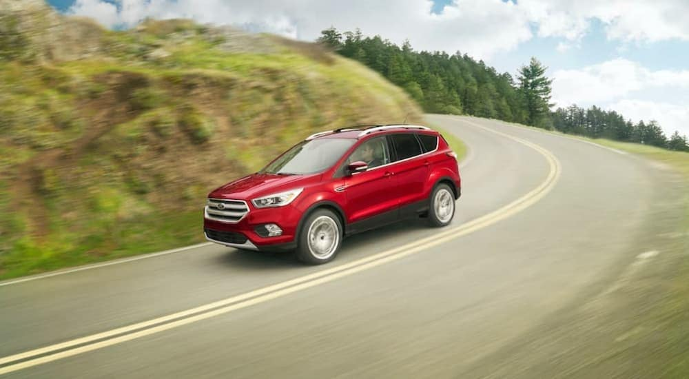A red 2018 Ford Escape is shown driving around a corner after leaving a pre-owned Ford dealer.