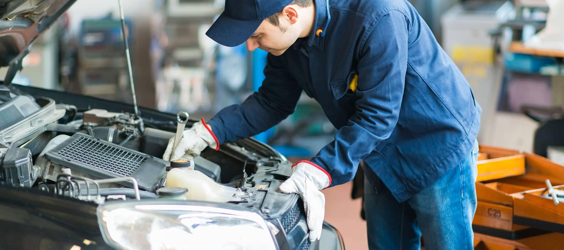 Service picture of technician working on car engine with a wrench