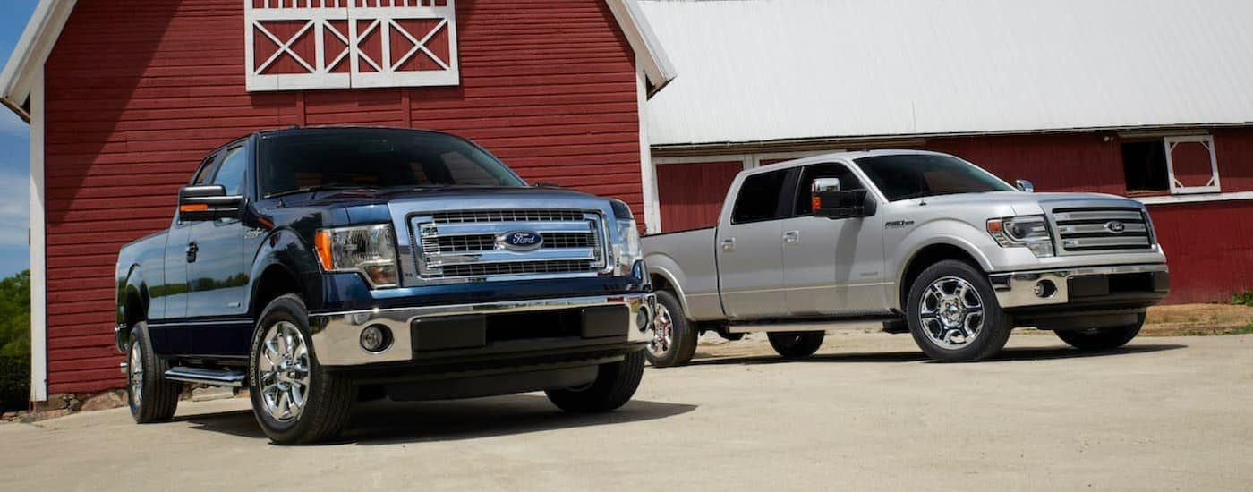 A black 2014 Ford F-150 XLT and silver Lariat are shown parked next to each other in front of a red barn.