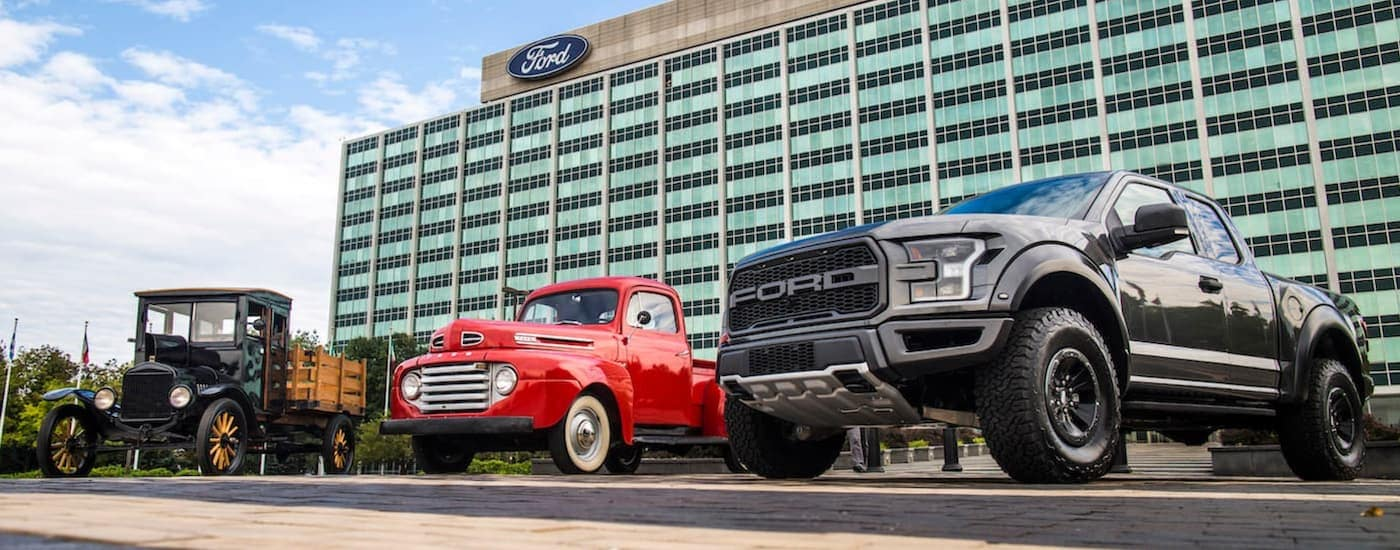 A 1917 Ford Model TT is shown parked next to two other F-Series trucks in front of the Ford building.