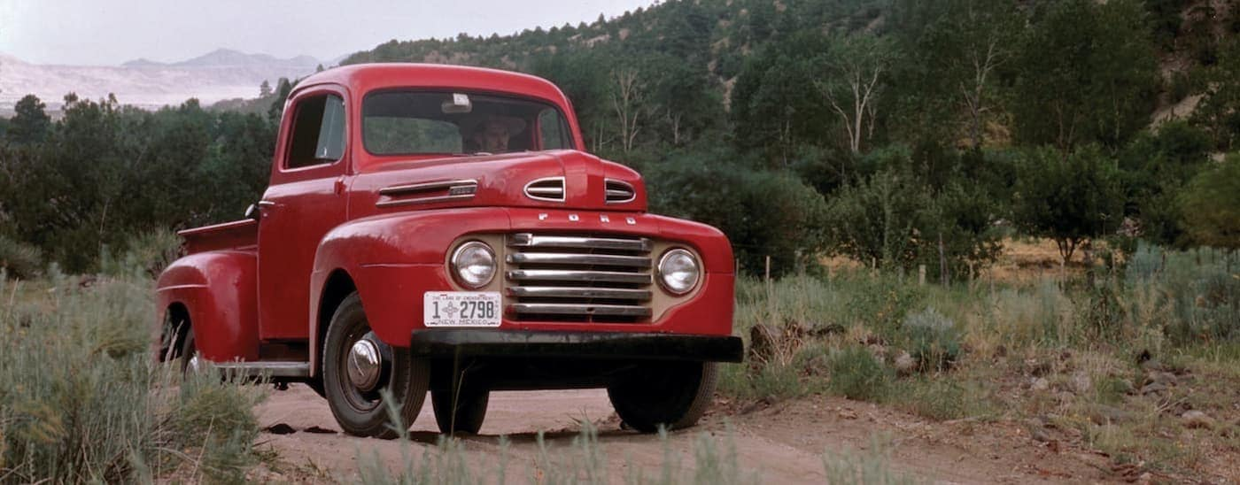 A red 1948 Ford F-1 is parked on a dirt path near a wooded hill.