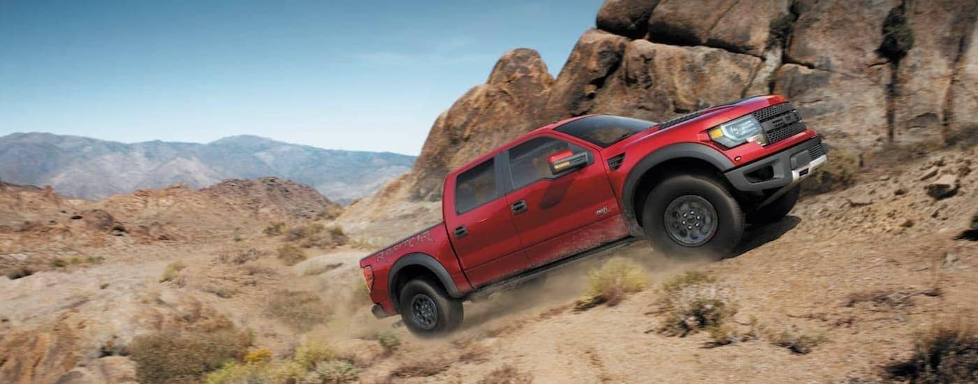 A red 2014 Ford Raptor SVT is shown driving up a dusty hill past a rock face.
