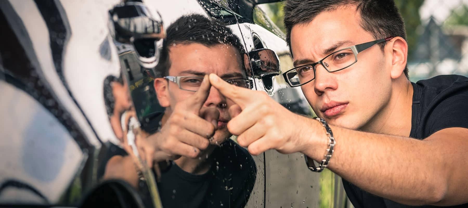 man wiping his fingure on super shiny car door