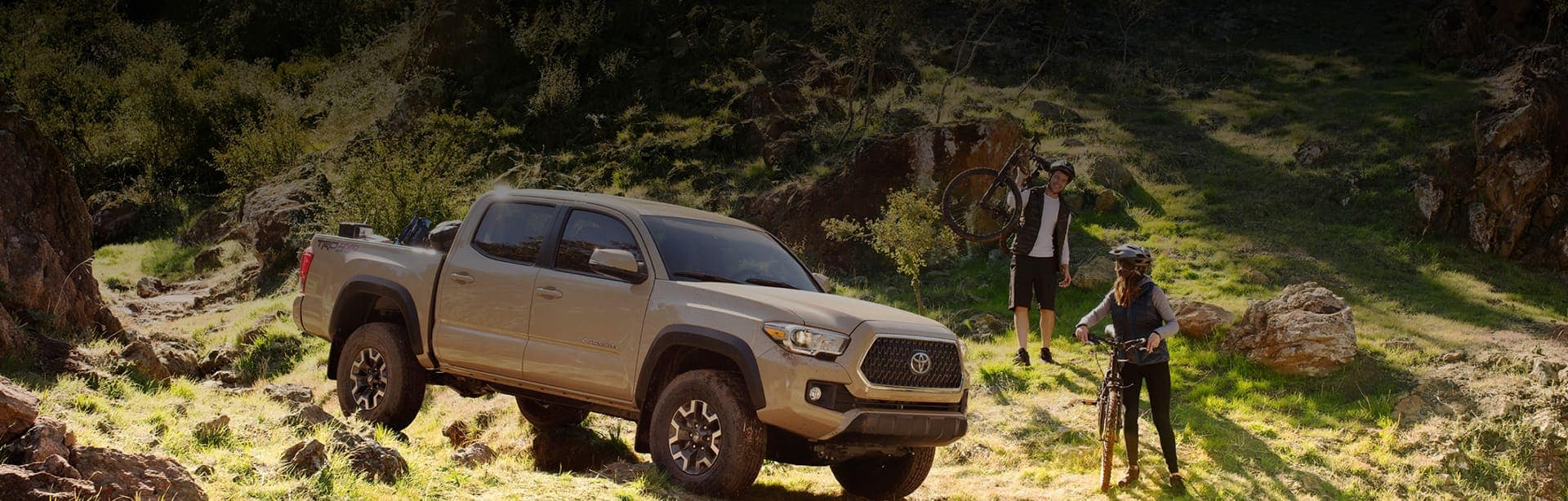 Two cyclists outdoors on a hill next to their Toyota Tacoma