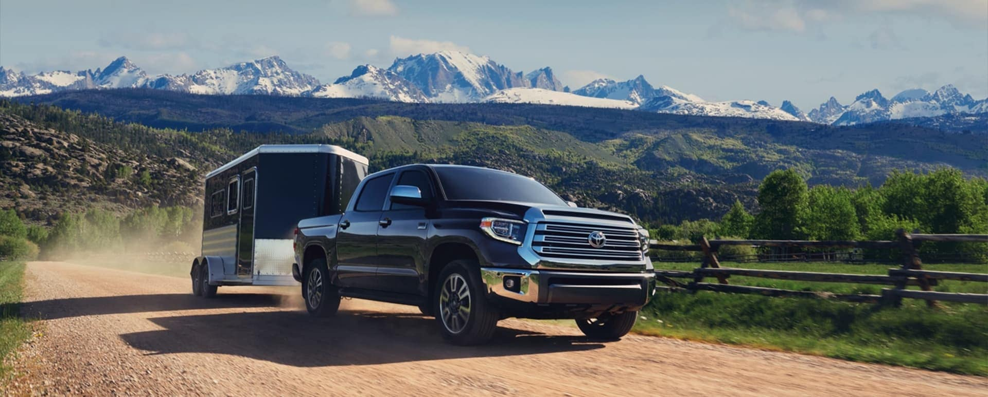 Black Toyota pickup truck hauling a trailer with hills and mountains in the background