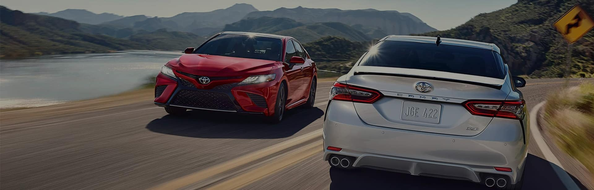 Alt Text: On a sunny day over looking a lake two Toyota camrys - one red - the other silver - pass each other as they glimmer in the sunlight - but the image has a dark hue