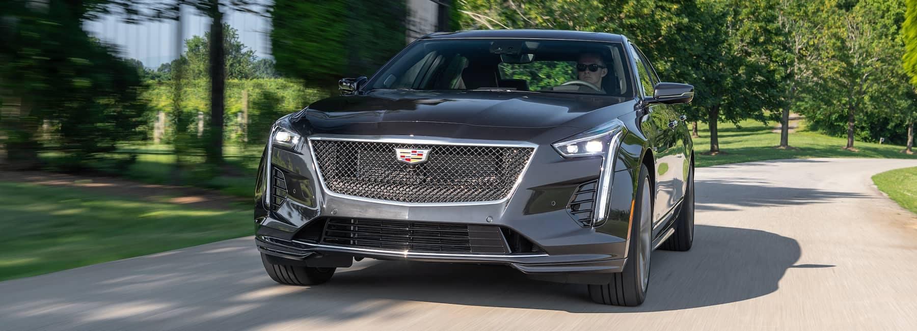 Cadillac Banner Image - Black Cadillac Sedan driving down a street