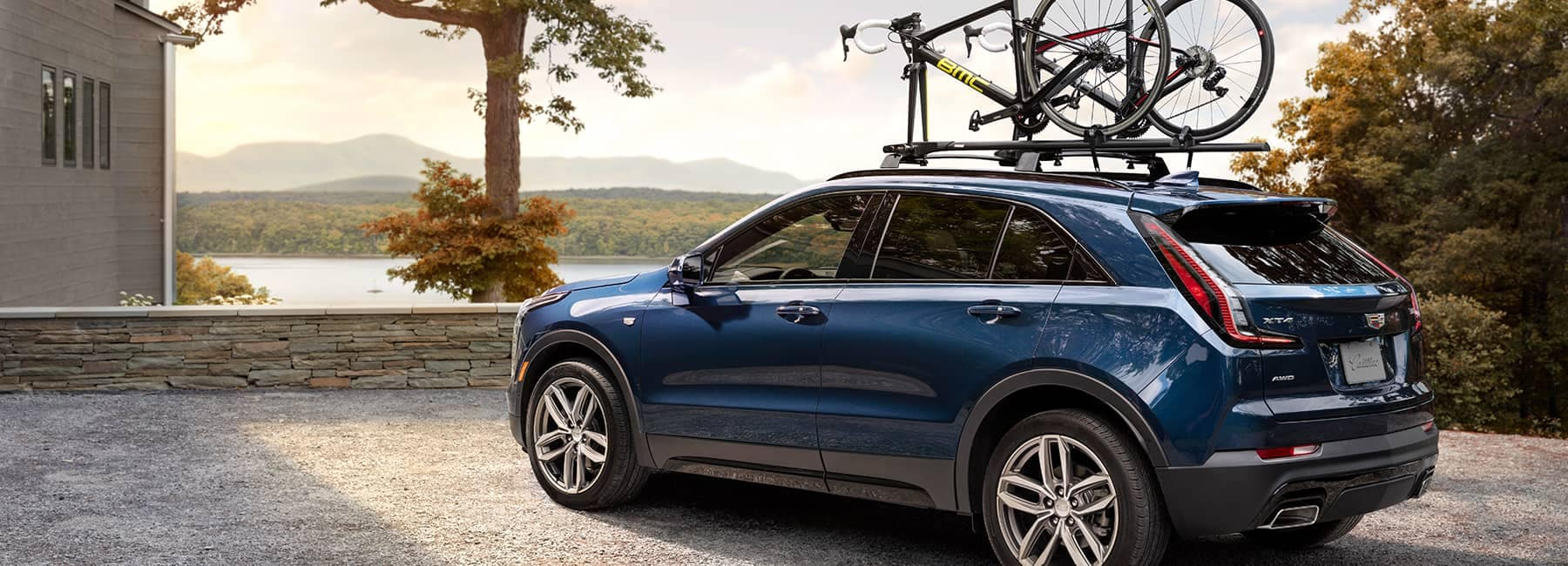 Cadillac Banner Image - A royal Blue Cadillac SUV/Crossover with a bike on the roof rack parked at a lake