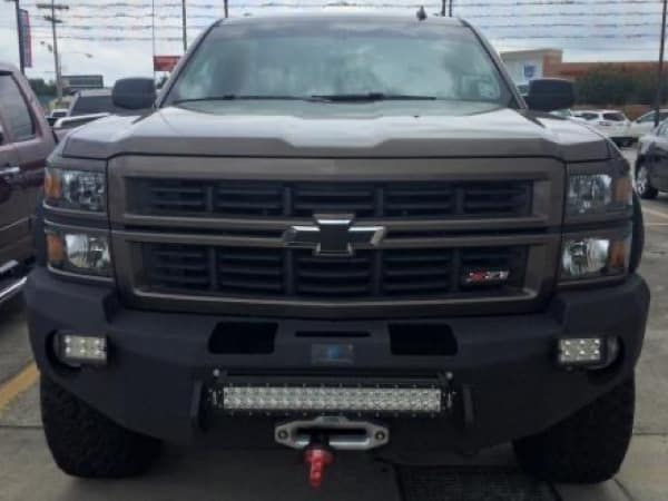 The customized grill of a dark green Chevy truck