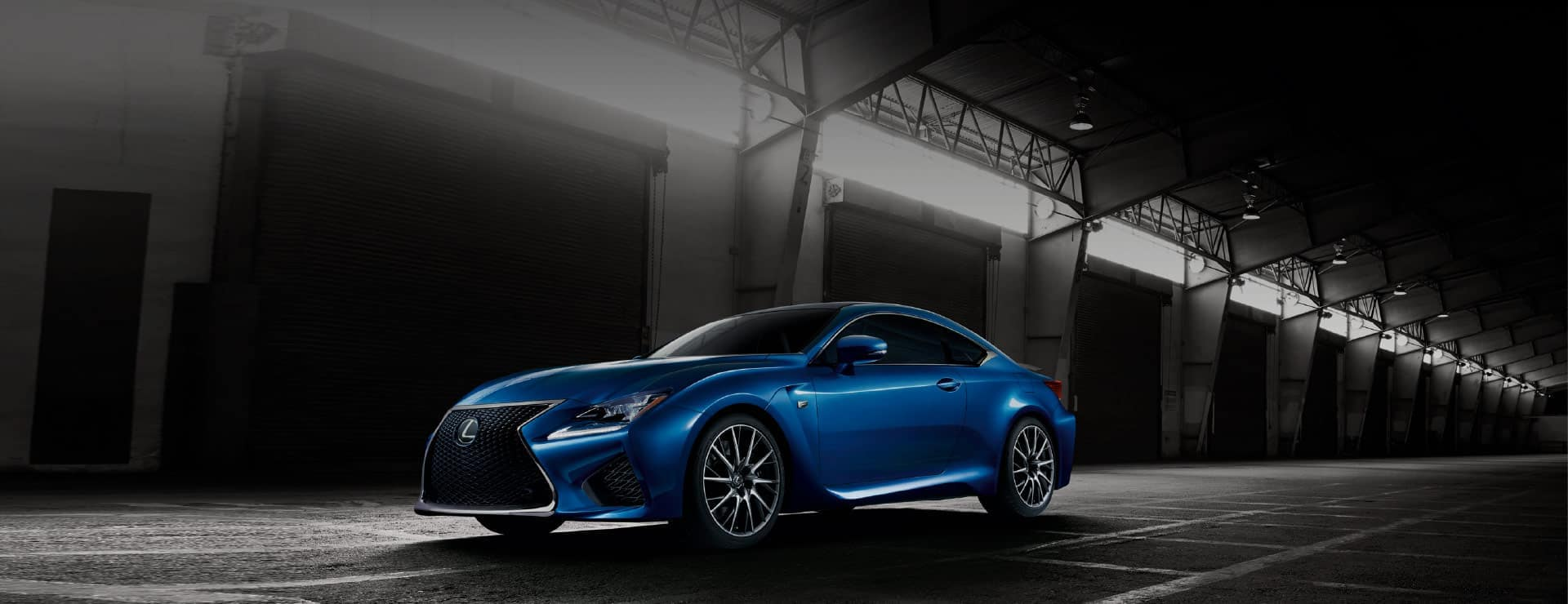 Blue Lexus Coupe in an empty greyscale industrial warehouse