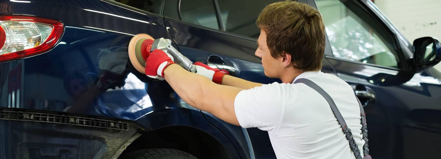 Mechanic performing body work to a car