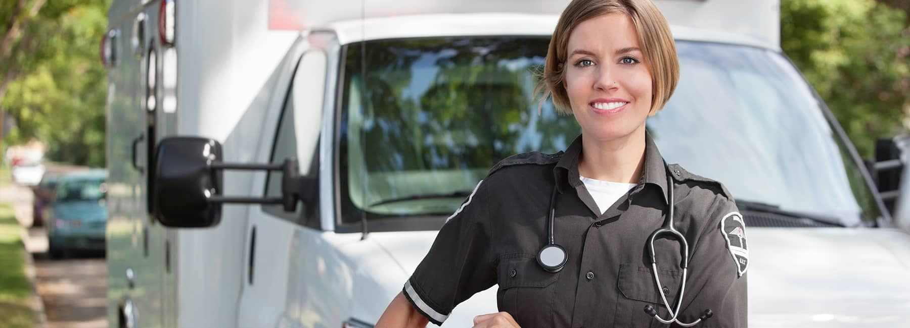 smiling first responder wearing stethoscope stands in front of ambulance