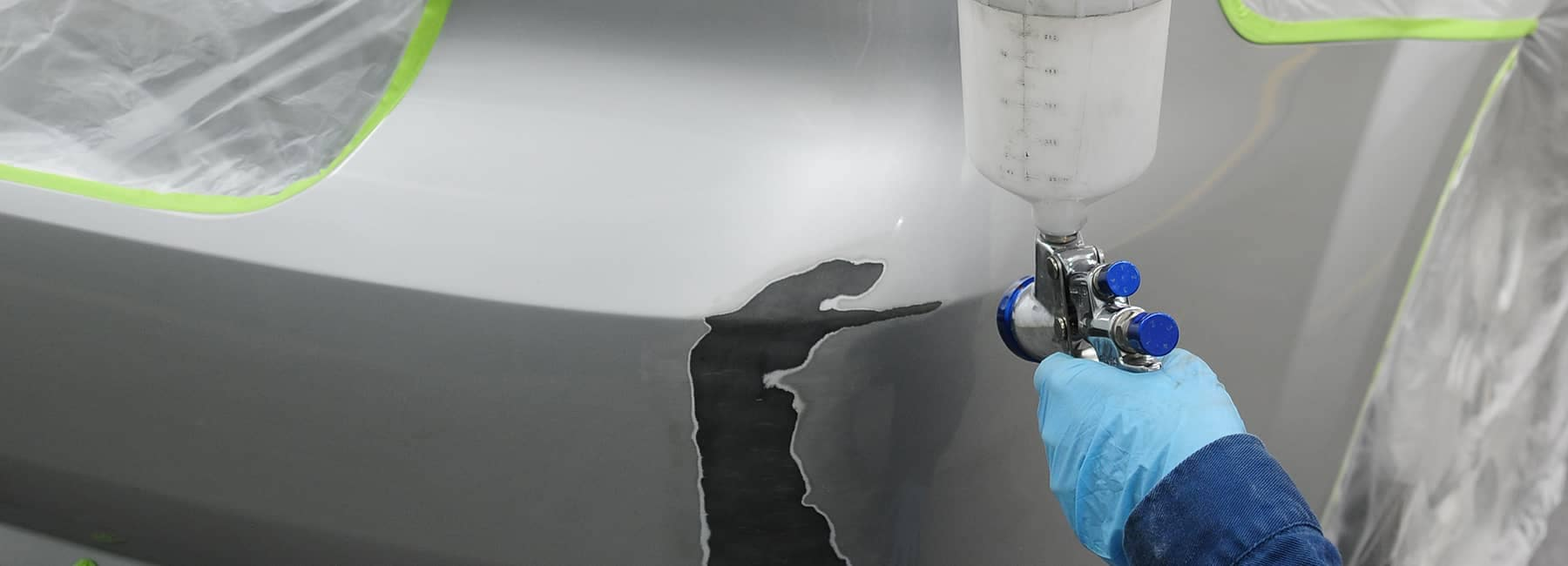 technician gets ready to spray paint on car body repair