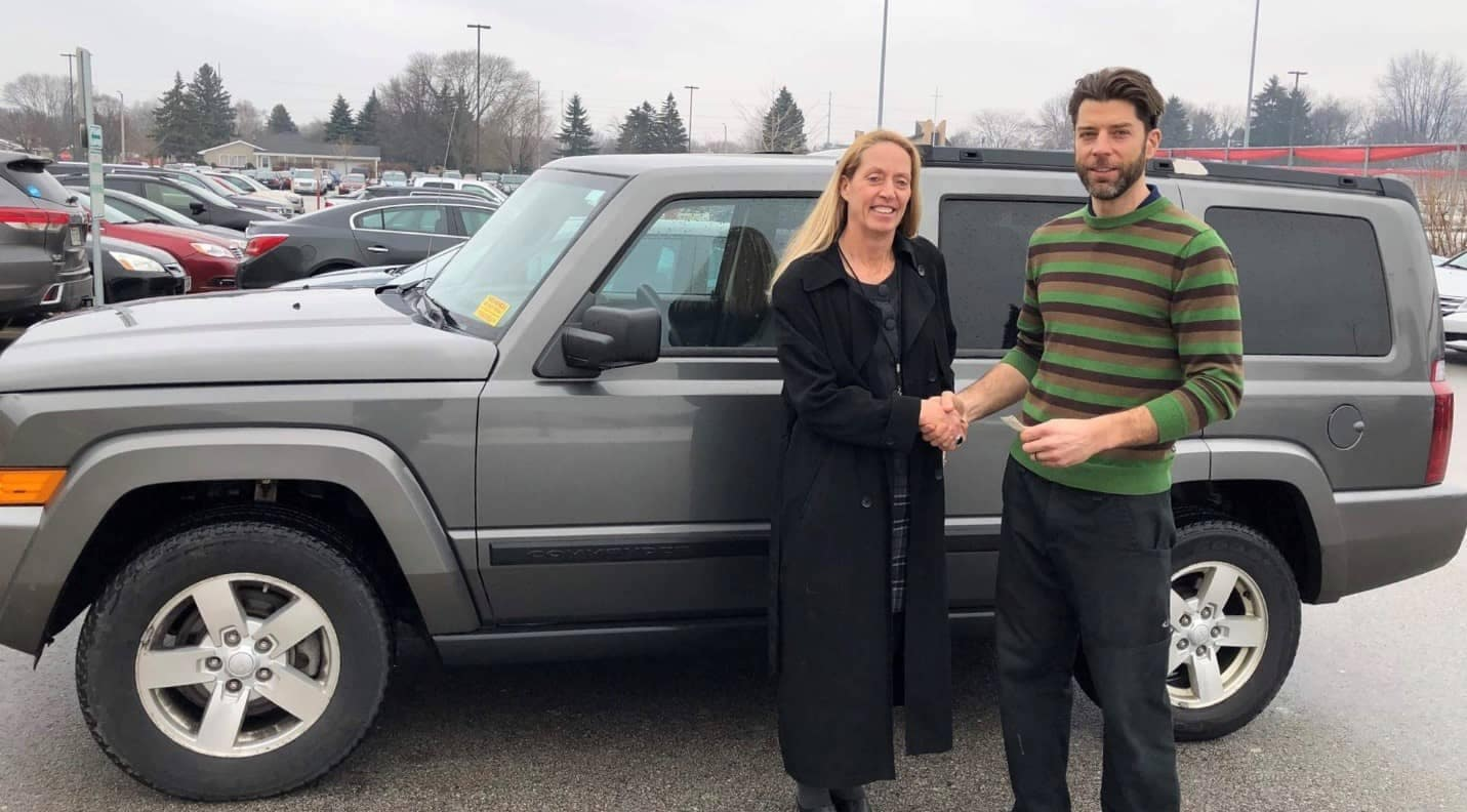 shaking hands in front of vehicle