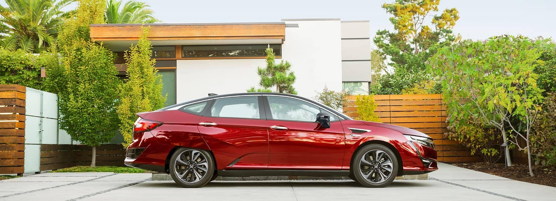 Sideview of a 2020 Red Honda Clarity Parked in a very nice Garage