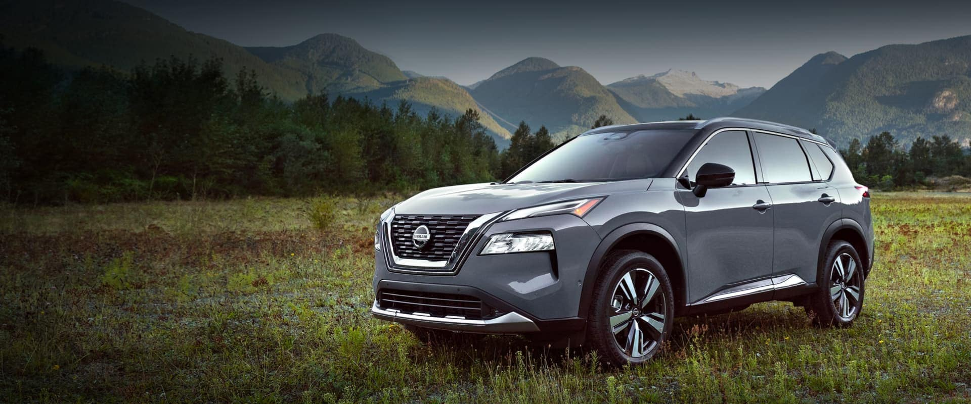 Light gray Nissan crossover in a field with mountains in the background