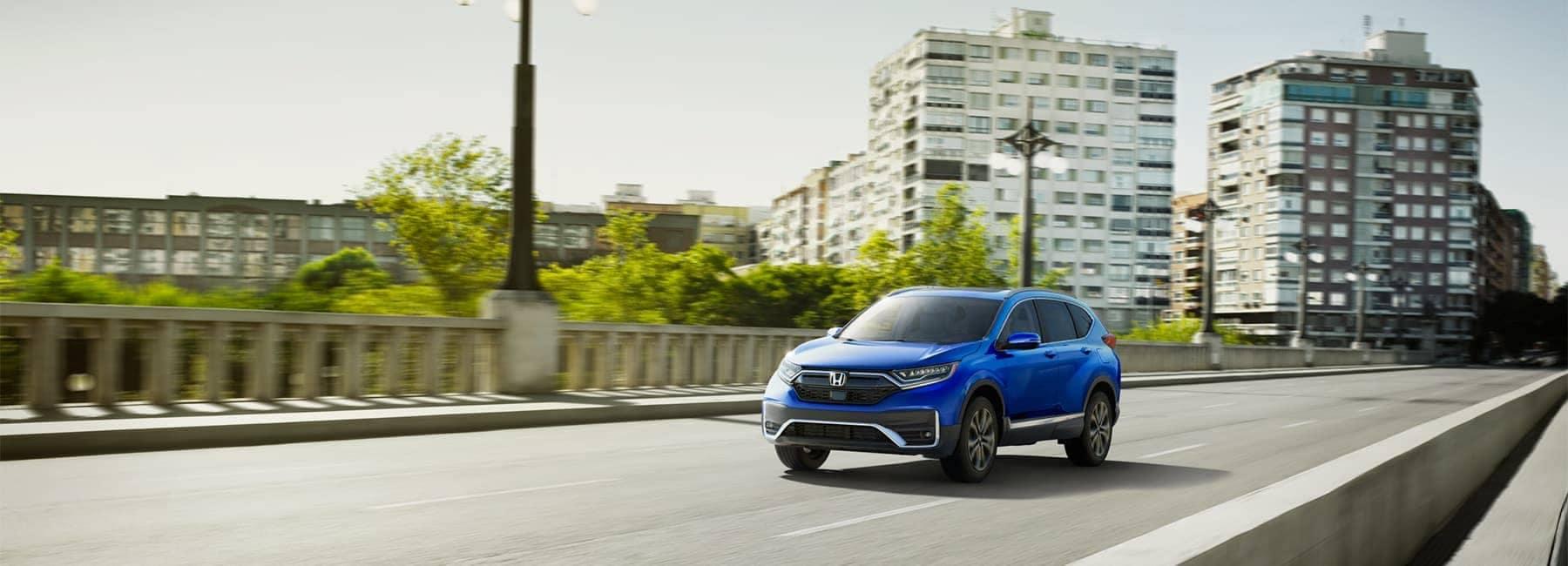 2020 Blue Honda CR-V driving down a two lane road