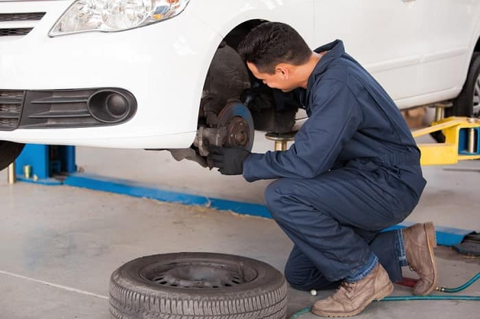 Mechanic_Fixing_Brakes_On_Car