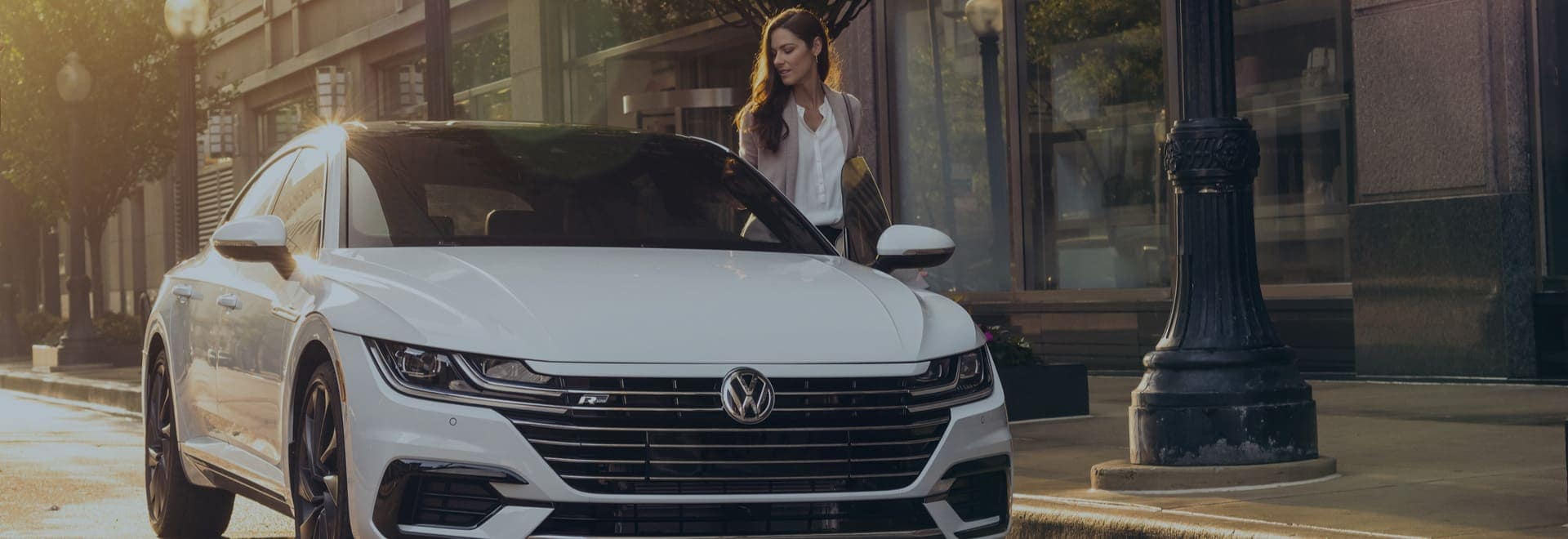 A woman is getting into the driver's side of a white VW sedan