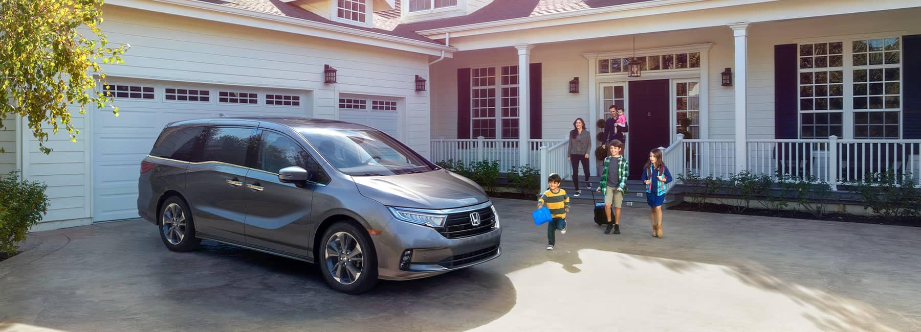 2021 Silver Honda Odyssey parked in front of a white home with black shutters