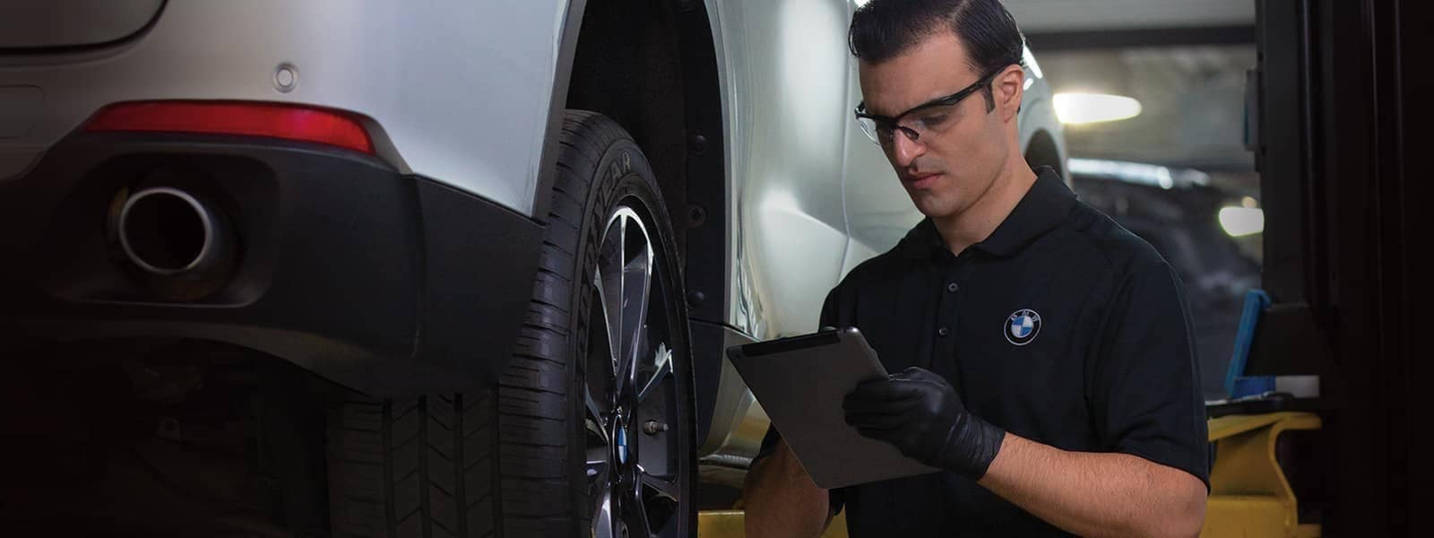 BMW Service Technician in service bay inspecting a BMW on a lift